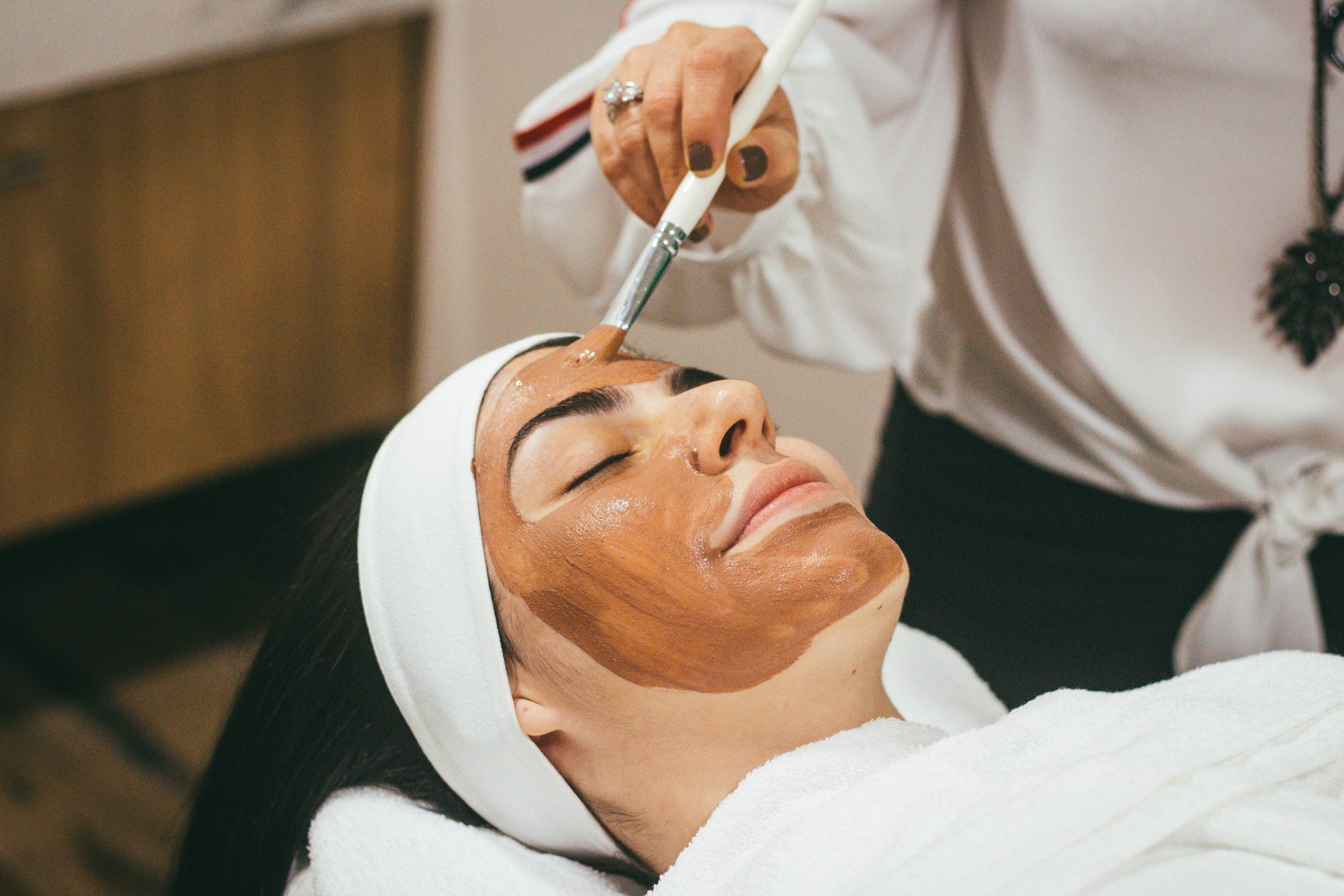 A woman applying face mask on another lady as one of the simple tips to improve your natural beauty